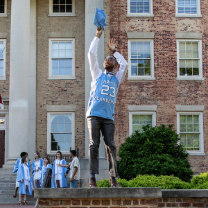 A Carolina senior poses in a number 23 basketball jersey