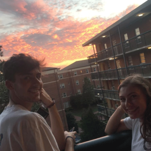 Photo of students enjoying a sunset view from a balcony on south campus