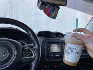 ice coffee being held up inside a car